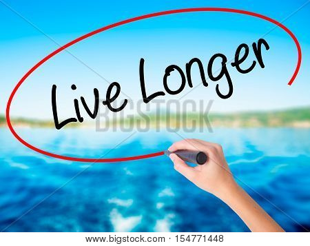 Woman Hand Writing Live Longer With A Marker Over Transparent Board