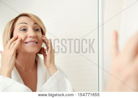 Senior woman doing facial anti aging massage near mirror