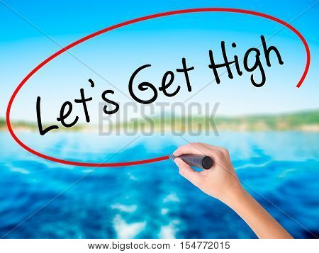Woman Hand Writing Let's Get High With A Marker Over Transparent Board