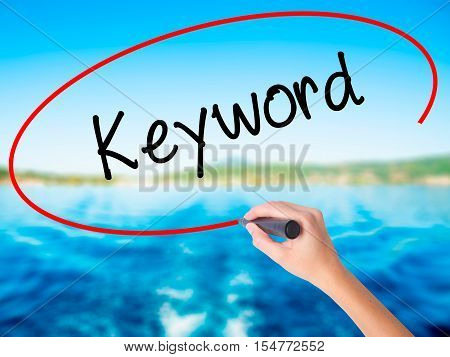 Woman Hand Writing Keyword With A Marker Over Transparent Board
