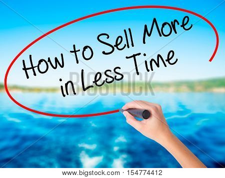 Woman Hand Writing How To Sell More In Less Time With A Marker Over Transparent Board.