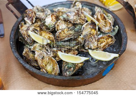 Fresh grilled oysters at grill pan. Seafood delicacy barbecue outdoors. Picnic healthy food, oysters in shells cooked at large metallic pan with lemon slices. Mediterranean cuisine