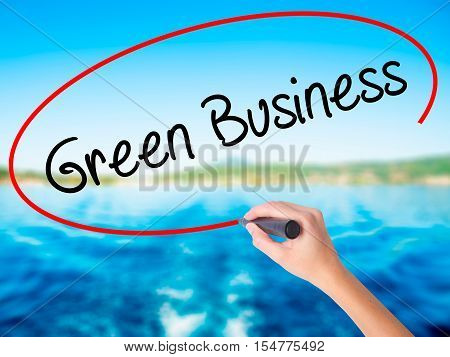 Woman Hand Writing Green Business With A Marker Over Transparent Board