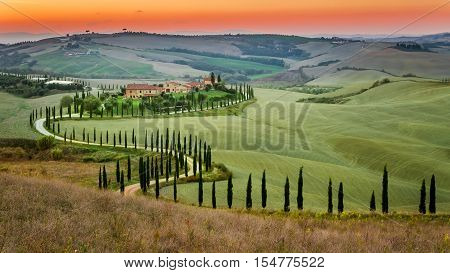 Sunset And Winding Road With Cypresses In Tuscany