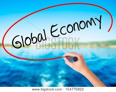 Woman Hand Writing Global Economy With A Marker Over Transparent Board