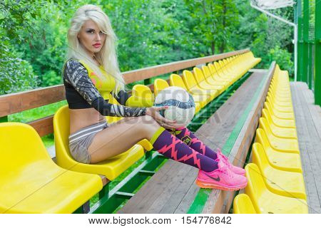 MOSCOW - JUL 16, 2015: Woman (with model release) with ball in her hands in resting on bench near football field