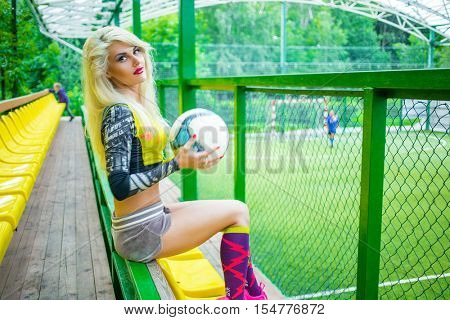 MOSCOW - JUL 16, 2015: beautiful woman (with model release) with ball in yellow top resting on bench near football field