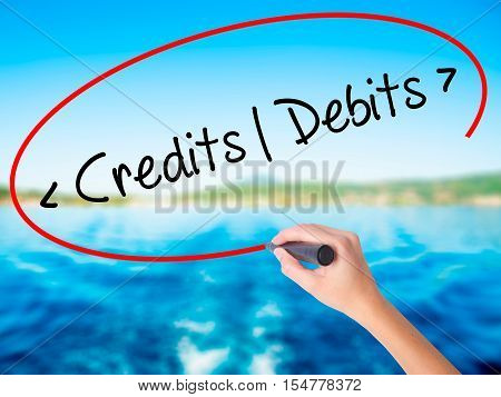 Woman Hand Writing Credits - Debits With A Marker Over Transparent Board.