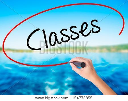 Woman Hand Writing Classes   With A Marker Over Transparent Board