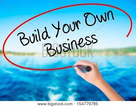Woman Hand Writing Build Your Own Business With A Marker Over Transparent Board.