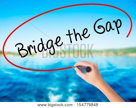 Woman Hand Writing Bridge The Gap With A Marker Over Transparent Board