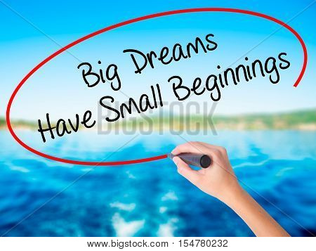 Woman Hand Writing Big Dreams Have Small Beginnings With A Marker Over Transparent Board