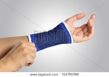 hand with a orthopedic wrist brace on gradient background