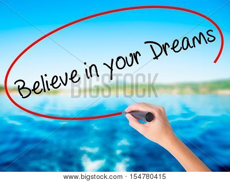 Woman Hand Writing Believe In Your Dreams With A Marker Over Transparent Board
