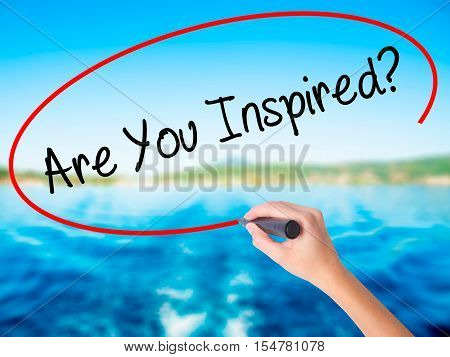 Woman Hand Writing Are You Inspired? With A Marker Over Transparent Board