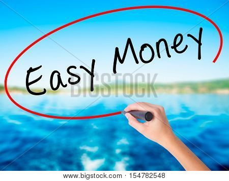 Woman Hand Writing Easy Money With A Marker Over Transparent Board
