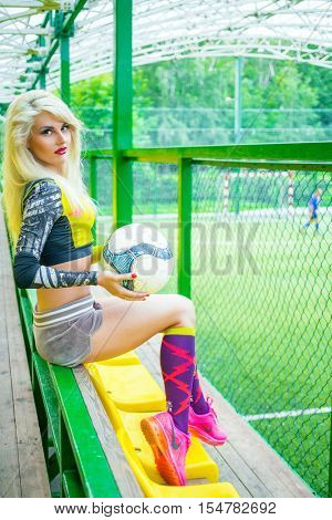 MOSCOW - JUL 16, 2015: woman (with model release) with ball in hands in yellow top and pink sneakers resting on bench