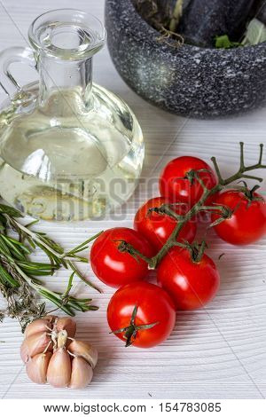 tomato with olive oil, garlic, rosemary, pounder on wooden background