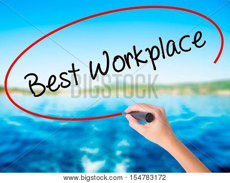 Woman Hand Writing Best Workplace With A Marker Over Transparent Board