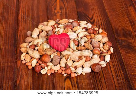 Different kinds of nuts, peeled, whole against the background of dark wood.