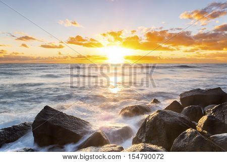 Sunrise over the ocean, with water cascading over the rocks at Burleigh Headland