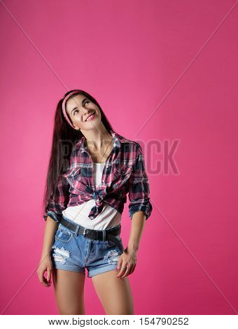 the cheerful girl in a plaid shirt on a pink background