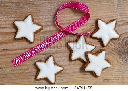 Cinnamon Star On Wood With Frohe Weihnachten (in German Merry Christmas) Gift Ribbon