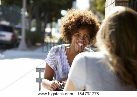 Two female friends sitting at a table outside a cafe