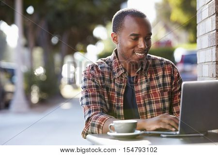 Young black man using a laptop computer outside a cafe