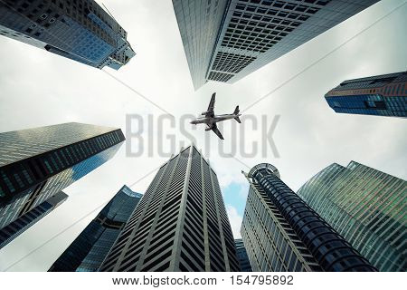 Singapore city buildings and a plane flying overhead in morning at Singapore