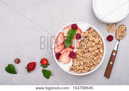 Granola for breakfast with berries yogurt and milk on grey stone background. Healthy eating oatmeal. Concept healhy lifestyle and diet. Top view