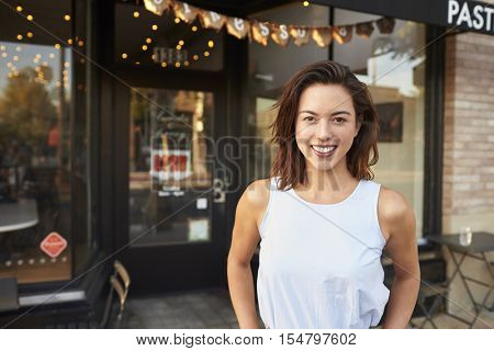 Female business owner standing in the street outside cafe