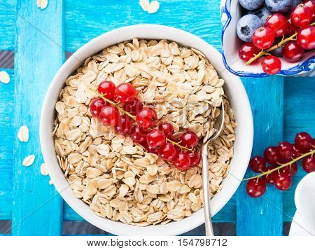 Bowl with rolled oats with red currants for healthy breakfast on bright blue wooden background. Top view
