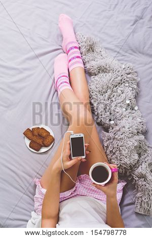 Young woman lying on bed with smart phone, tea of coffee, and cookies in bed, with cookies and woolen blanket next to her. High angle, top view. Matte filter.