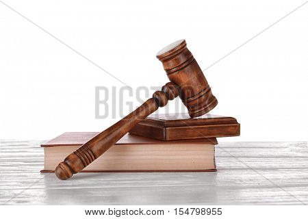 Gavel with sound block on book on white background