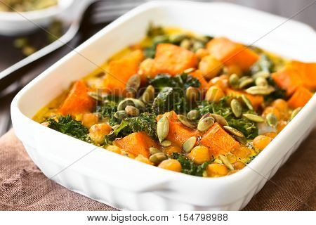 Baked pumpkin kale and chickpea casserole with pumpkin seeds on top in casserole dish photographed with natural light (Selective Focus Focus one third into the image)