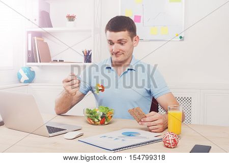 Man surprised of his healthy business lunch in modern office. Young handsome businessman in casual at working place, look at fork displeased with vegetable salad bowl, diet and eating right concept.