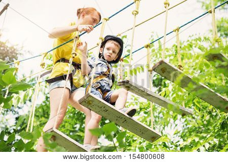 Kids climbing in adventure park. Boy enjoys climbing in the ropes course adventure. Child climbing high wire park. Happy boys playing at adventure park holding ropes and climbing wooden stairs.