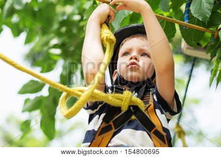Boy Enjoys Climbing In The Ropes Course Adventure. Smiling Child Engaged Climbing High Wire Park