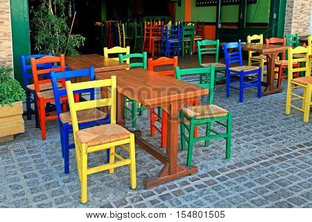 traditional sidewalk greek tavern with wood table and multicolored chairs, Crete, Greece.