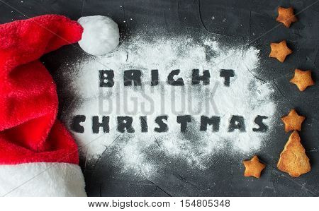 christmas background with Santa's cap and baked gingerbread stars and christmas tree with words bright christmas made from powdered sugar on the concrete background. creative idea