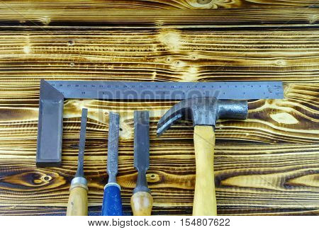 Basic carpenter tools on wooden table as background