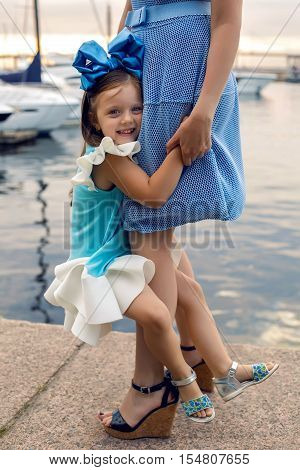 little girl three years sitting on my mother's hands with long blond hair and they are dressed in blue dress and large blue bow on her head , sitting at the pier on the sea with a yacht during sunset