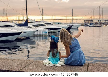 mom shows daughter three years ships in a blue dress and blue big bow sitting on the dock by the sea with yachts at sunset