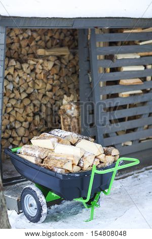 Firewood stacked in winter. Wood pile with snow stacked for firewood. Cart with wood.
