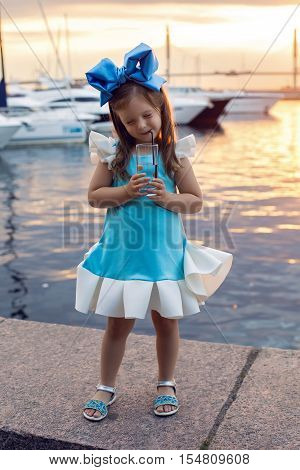 portrait of a little girl three years with the blue bow on her head, stands near the water and near the dock where there are boats at sunset in the summer, drinking a glass of water through a straw