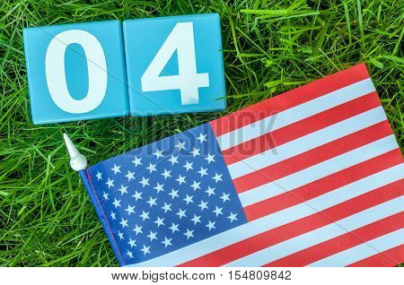 July 4th wooden color calendar with Stars and Stripes flag on green grass background. Summer day. Empty space for text. Independence Day Of America.