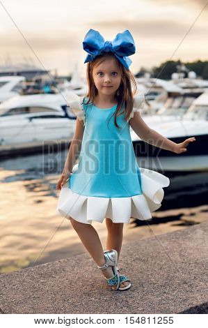 portrait of a little girl three years with the blue bow on her head, stands near the water and near the dock where there are boats at sunset in the summer