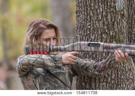 Woman wearing camoflauge shirt aiming a shotgun hunting
