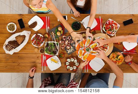 People eat grilled corn at festive table served for party. Friends celebrate with catering food on wooden table top view. Woman and man's hands take the corncobs.